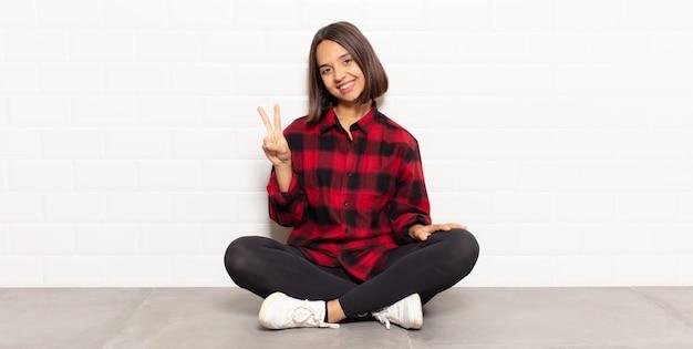 Latynoska kobieta uśmiecha się i wygląda przyjaźnie, pokazując numer dwa lub sekundę z ręką do przodu, odliczając w dół