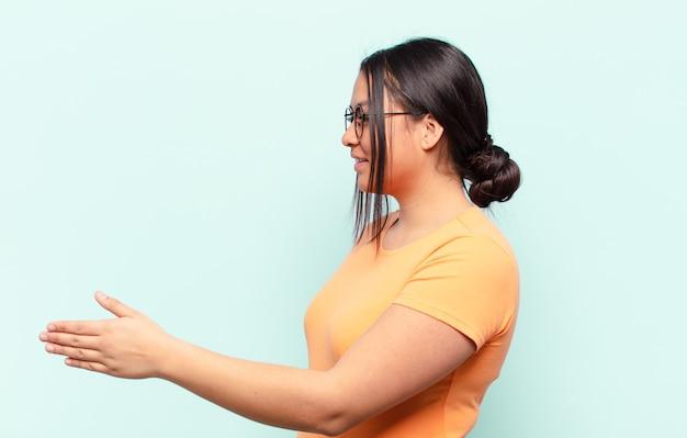 Latynoska kobieta uśmiecha się, wita i oferuje uścisk dłoni, aby sfinalizować udaną transakcję, koncepcja współpracy