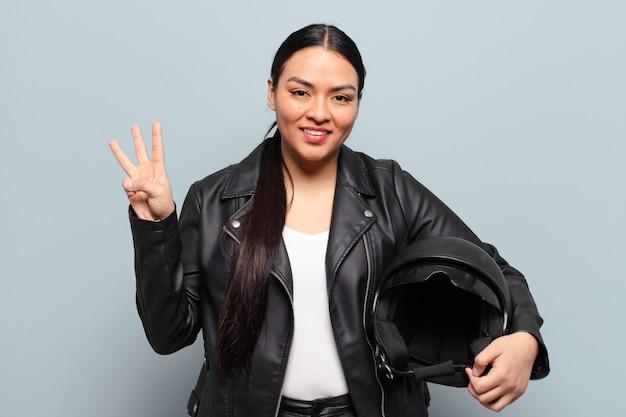 Latynoska kobieta uśmiechnięta i wyglądająca przyjaźnie, pokazująca cyfrę trzy lub trzecią z ręką do przodu, odliczająca
