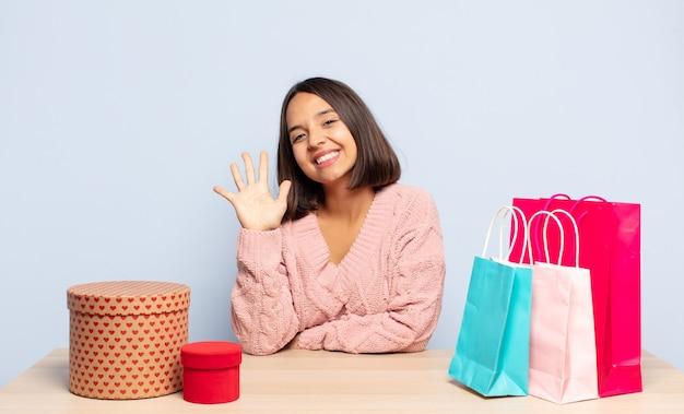 Latynoska kobieta uśmiechnięta i wyglądająca przyjaźnie, pokazująca numer pięć lub piąty z ręką do przodu, odliczający