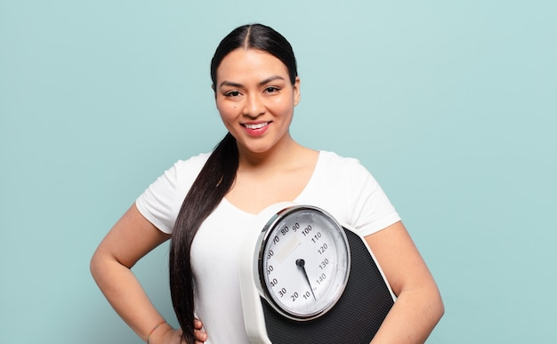 Latynoska kobieta uśmiechnięta radośnie z ręką na biodrze i pewną siebie, pozytywną, dumną i przyjazną postawą