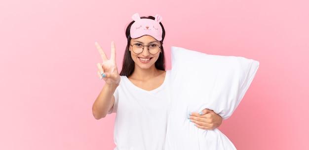 Latynoska kobieta w piżamie uśmiechnięta i wyglądająca na szczęśliwą, gestykulująca zwycięstwo lub pokój i trzymająca poduszkę