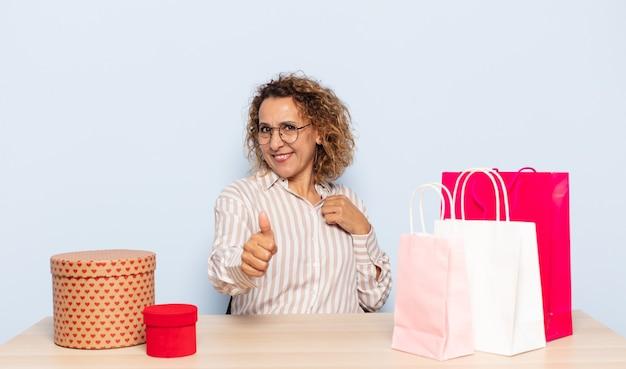 Latynoska kobieta w średnim wieku czująca się dumna, beztroska, pewna siebie i szczęśliwa, uśmiechająca się pozytywnie z uniesionymi kciukami