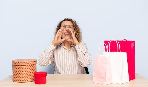 Latynoska kobieta w średnim wieku czująca się szczęśliwa, podekscytowana i pozytywna, wydająca głośny okrzyk z rękami przy ustach, wzywająca
