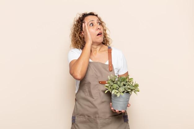 Latynoska kobieta w średnim wieku czująca się szczęśliwa, podekscytowana i zaskoczona, patrząc w bok z obiema rękami na twarzy