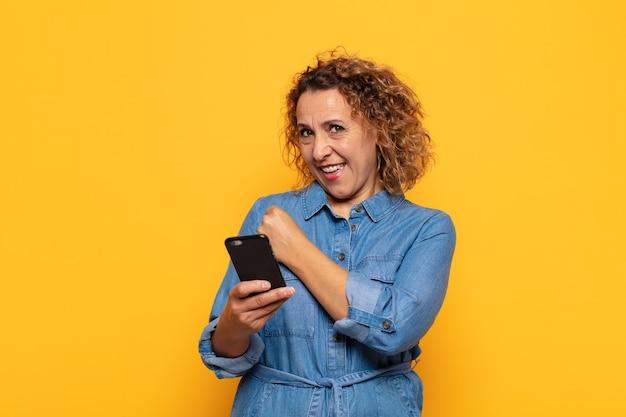 Latynoska kobieta w średnim wieku czująca się szczęśliwa, pozytywna i odnosząca sukcesy, zmotywowana, gdy staje przed wyzwaniem lub świętuje dobre wyniki