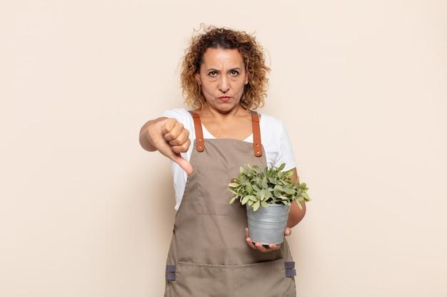 Latynoska kobieta w średnim wieku czująca się zła, zła, zirytowana, rozczarowana lub niezadowolona, pokazująca kciuki w dół z poważnym spojrzeniem
