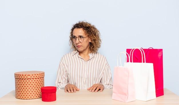 Latynoska kobieta w średnim wieku czuje się smutna, zdenerwowana lub zła i patrzy w bok z negatywnym nastawieniem