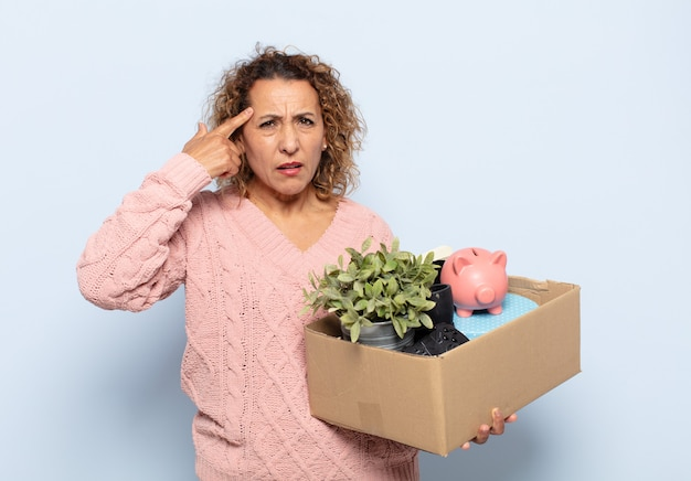 Latynoska kobieta w średnim wieku czuje się zdezorientowana i zdziwiona, pokazując, że jesteś szalony, szalony lub oszalały