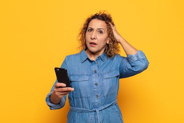Latynoska kobieta w średnim wieku czuje się zestresowana, zmartwiona, niespokojna lub przestraszona, z rękami na głowie, panikuje z powodu błędu