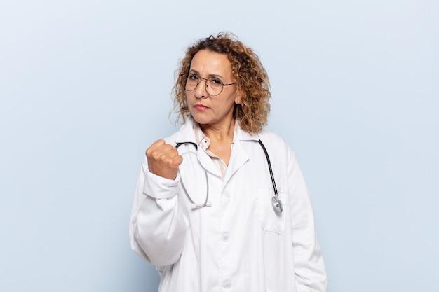 Latynoska kobieta w średnim wieku czuje się zła, zirytowana, zbuntowana i agresywna, macha środkowym palcem, walczy