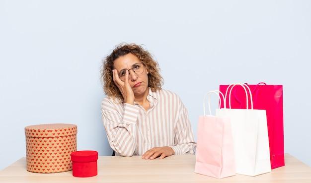 Latynoska kobieta w średnim wieku czuje się znudzona, sfrustrowana i senna po męczącym, nudnym i żmudnym zadaniu, trzymając twarz dłonią