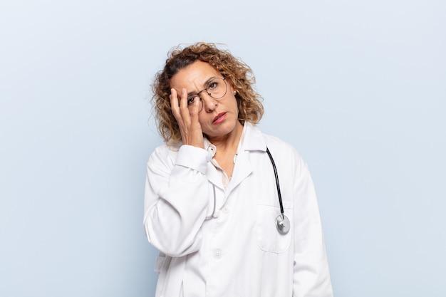 Latynoska kobieta w średnim wieku czuje się znudzona, sfrustrowana i senna po męczącym, nudnym i żmudnym zadaniu, trzymając twarz ręką