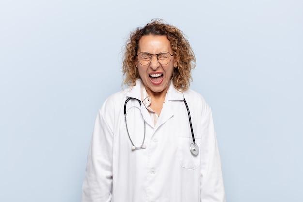 Latynoska kobieta w średnim wieku krzycząca agresywnie, wyglądająca na bardzo zła, sfrustrowana, oburzona lub zirytowana, krzycząca nie