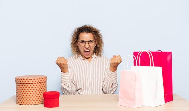 Latynoska kobieta w średnim wieku, krzycząca agresywnie z gniewnym wyrazem twarzy lub z zaciśniętymi pięściami świętująca sukces