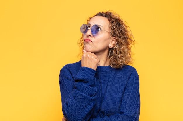 Latynoska kobieta w średnim wieku myśli, czuje się niepewna i zdezorientowana, ma różne opcje, zastanawiając się, jaką decyzję podjąć