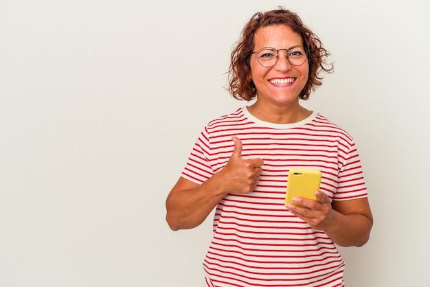 Latynoska kobieta w średnim wieku na białym tle uśmiechnięta i unosząca kciuk w górę