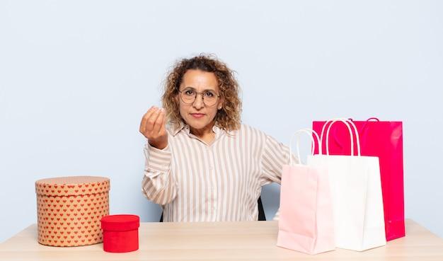Latynoska kobieta w średnim wieku robiąca kaprysy lub gesty pieniężne, każąc ci spłacić swoje długi!