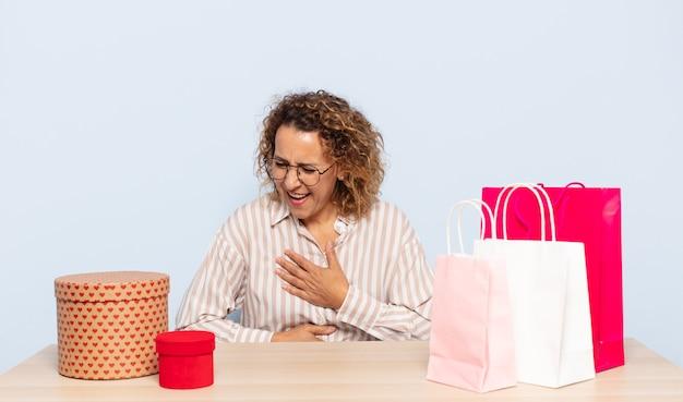 Latynoska kobieta w średnim wieku śmiejąca się głośno z jakiegoś przezabawnego żartu, czująca się szczęśliwa i wesoła, dobrze się bawiąca