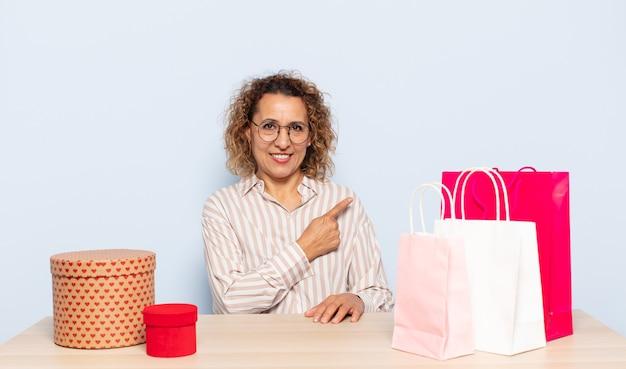 Latynoska kobieta w średnim wieku uśmiecha się radośnie, czuje się szczęśliwa i wskazuje na bok i do góry, pokazując obiekt w przestrzeni kopii