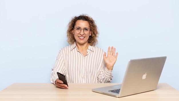 Latynoska Kobieta W średnim Wieku Uśmiecha Się Radośnie I Wesoło, Macha Ręką, Wita I Wita Lub żegna Się Premium Zdjęcia