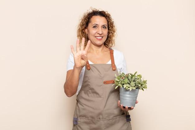 Latynoska kobieta w średnim wieku, uśmiechnięta i przyjazna, pokazująca cyfrę cztery lub czwarte z ręką do przodu, odliczająca w dół