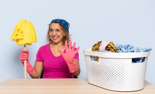 Latynoska kobieta w średnim wieku, uśmiechnięta i wyglądająca przyjaźnie, pokazująca cyfrę pięć lub piąta z ręką do przodu, odliczająca w dół