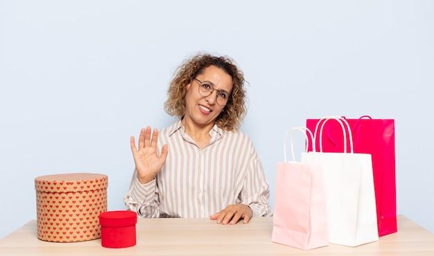 Latynoska kobieta w średnim wieku uśmiechnięta radośnie i wesoło, machająca ręką, witająca i witająca lub żegnająca się