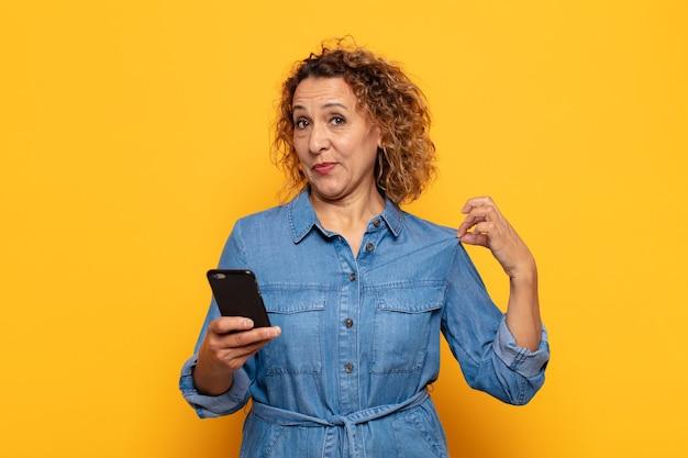 Latynoska kobieta w średnim wieku wyglądająca na arogancką, odnoszącą sukcesy, pozytywną i dumną, wskazującą na siebie
