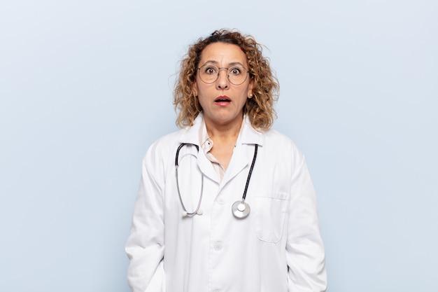 Latynoska kobieta w średnim wieku wyglądająca na bardzo zszokowaną lub zaskoczoną, z otwartymi ustami i mówiącą wow