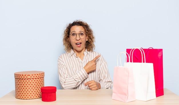 Latynoska kobieta w średnim wieku wyglądająca na podekscytowaną i zaskoczoną, wskazując na bok i do góry, aby skopiować miejsce