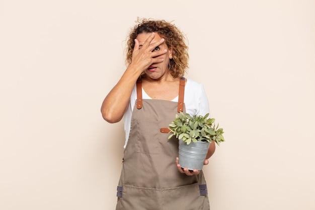 Latynoska kobieta w średnim wieku wyglądająca na zszokowaną, przestraszoną lub przerażoną, zakrywająca twarz dłonią i zaglądająca spomiędzy palców