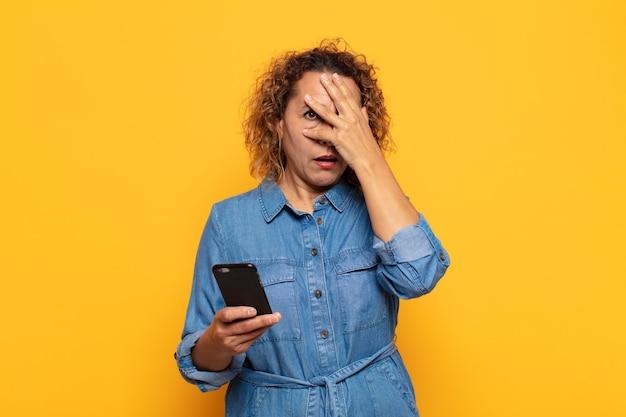 Latynoska kobieta w średnim wieku, wyglądająca na zszokowaną, przestraszoną lub przerażoną, zakrywająca twarz dłonią i zaglądająca spomiędzy palców