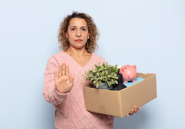 Latynoska kobieta w średnim wieku wyglądająca poważnie, surowo, niezadowolona i zła, pokazując otwartą dłoń, wykonując gest zatrzymania