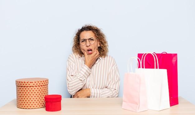 Latynoska kobieta w średnim wieku z szeroko otwartymi ustami i oczami i dłońmi na brodzie, czująca się nieprzyjemnie zszokowana, mówiąca co lub wow