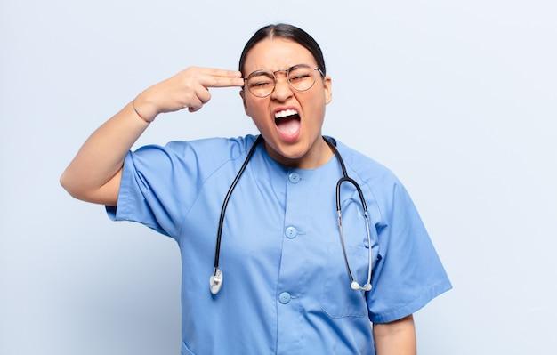 Latynoska kobieta wyglądająca na nieszczęśliwą i zestresowaną, samobójczy gest wykonujący znak pistoletu ręką, wskazujący na głowę
