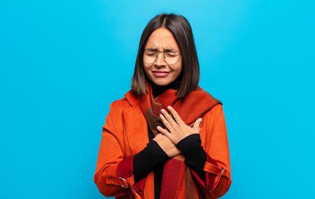 Latynoska kobieta wyglądająca na smutną, zranioną i załamaną, trzymająca obie ręce blisko serca, płaczącą i przygnębioną