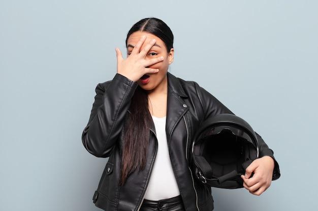 Latynoska kobieta wyglądająca na zszokowaną, przestraszoną lub przerażoną, zakrywającą twarz dłonią i zaglądającą spomiędzy palców