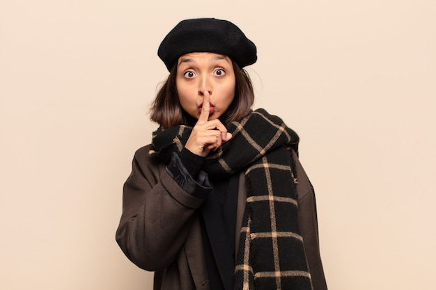 Latynoska kobieta wyglądająca poważnie i krzywo, z palcem przyciśniętym do ust, domagająca się ciszy lub spokoju, zachowująca tajemnicę