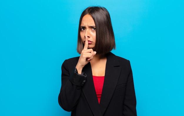 Latynoska kobieta wyglądająca poważnie i ze złością, z palcem przyciśniętym do ust, domagająca się ciszy lub spokoju, zachowująca tajemnicę