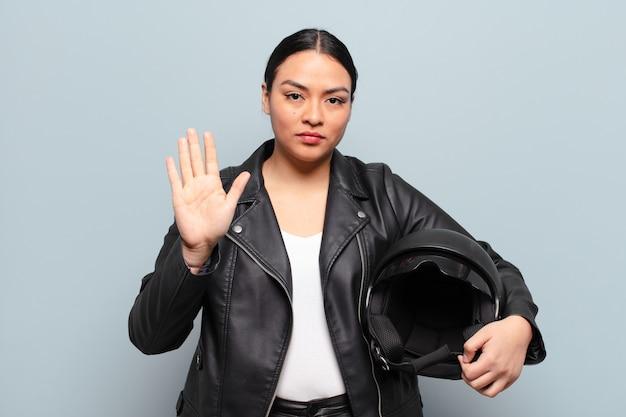 Latynoska kobieta wyglądająca poważnie, surowo, niezadowolona i zła, pokazująca otwartą dłoń wykonującą gest stop
