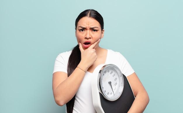 Latynoska kobieta z szeroko otwartymi ustami i oczami i ręką na brodzie, czująca się nieprzyjemnie zszokowana, mówiąca co lub wow