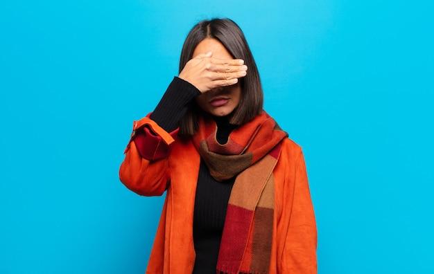 Latynoska kobieta zakrywająca oczy jedną ręką, czująca się przestraszona lub niespokojna, zastanawiająca się lub na ślepo czekająca na niespodziankę