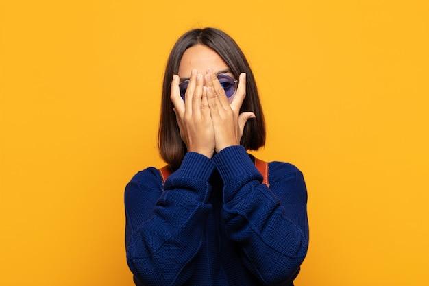 Latynoska kobieta zakrywająca twarz rękami, zaglądająca między palce z zaskoczeniem i patrząc w bok