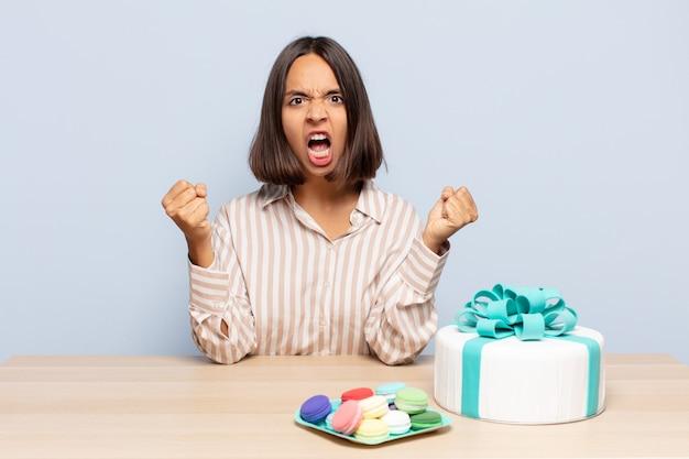 Latynoska krzycząca agresywnie z gniewnym wyrazem twarzy lub z zaciśniętymi pięściami świętująca sukces