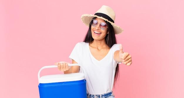 Latynoska ładna kobieta czuje się dumna, uśmiecha się pozytywnie z kciukami do góry z przenośną lodówką na piknik