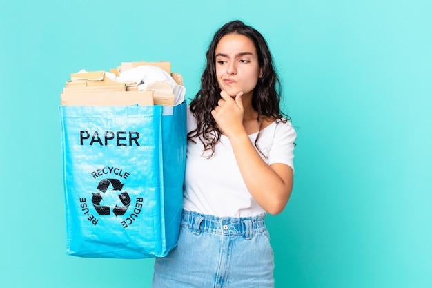 Latynoska ładna kobieta myśli, czuje się zwątpienie i zdezorientowana i trzyma papierową torbę z recyklingu