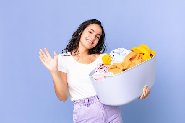 Latynoska ładna kobieta uśmiecha się radośnie, macha ręką, wita cię i wita i trzyma kosz na pranie