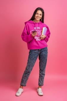 Latynoska ładna kobieta w różowej bluzie z kapturem, uśmiechnięta, trzymająca zeszyty i używająca smartfona pozującego na różowo