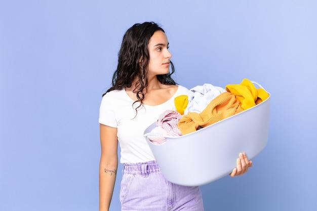 Latynoska ładna kobieta w widoku profilu myśląca, wyobrażająca sobie lub marząca na jawie i trzymająca kosz na pranie